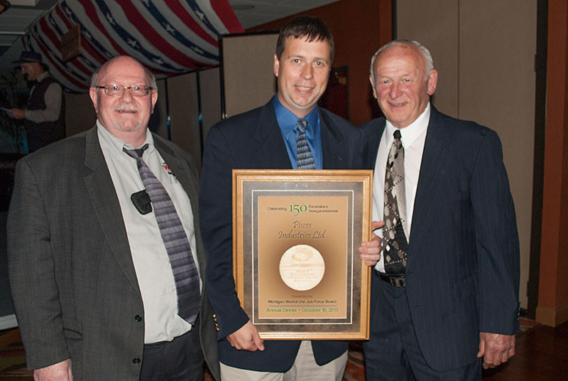 Matt Wastell, center, of Pisces Fish Machinery accepts the Delta Chamber of Commerce Business of the Year award from Orin Bailey, left, of Michigan Works! The Job Force Board and Wil Carne, Job Force Board member.