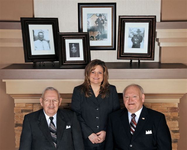 Don, Caren and James Crawford pose with photos of family members involved in the Crawford Funeral Home business over 150 years.