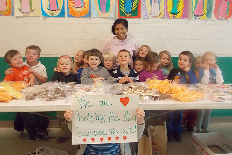 Pictured at the bake sale with Holy Name Catholic School's custodian, Nila, whose family home in the Philippines was partially destroyed by the recent earthquake, is Holy Name's Readiness Kindergarten class.